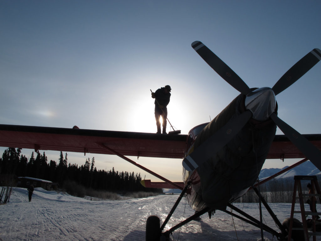 Paul Claus sweeps frost off the wing of the Turbine Otter at the Ultima Thule Lodge airstrip.