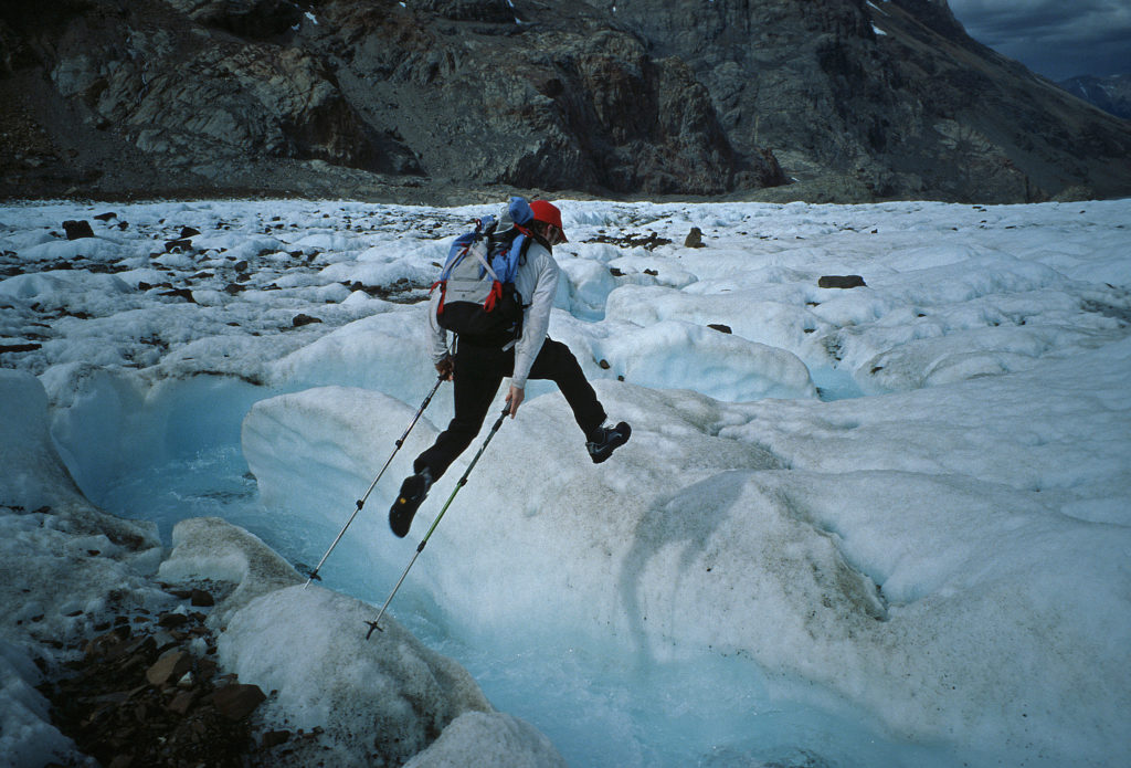 – Ben Ditto leaping across a gushing glacier river in the Rio Electico valley of Patagonia.