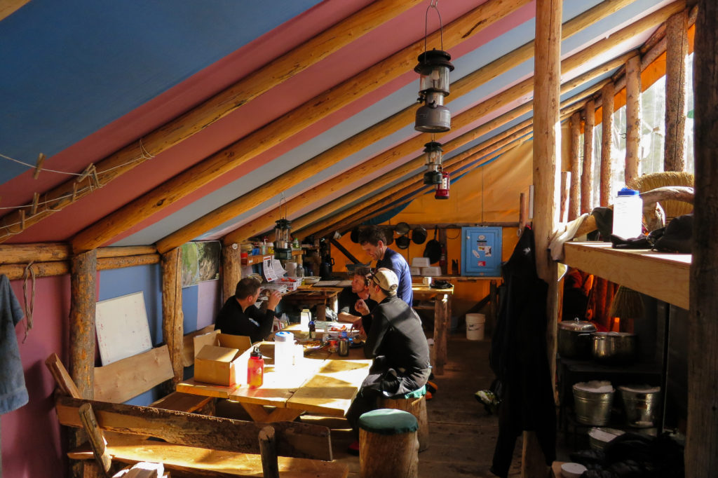 A guided group enjoys the warm winter sun inside the new hut