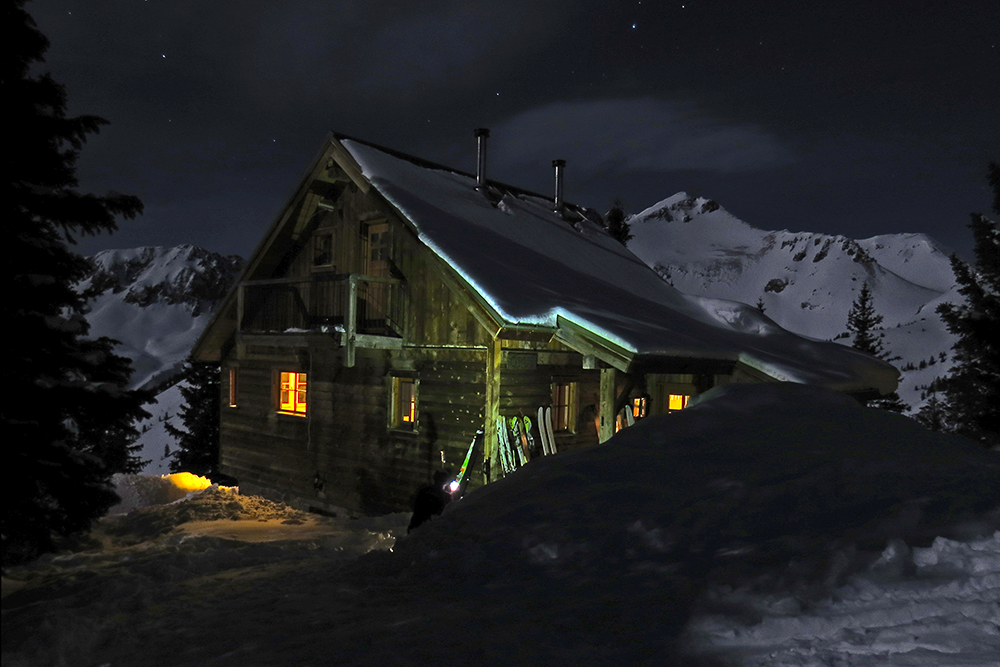 Opus hut illuminated beneath a full moon